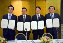 協定書に調印した関西電力の岩根社長(右から2人目)、青森県の三村知事(右)ら関係者