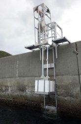 防波堤に設置した波力発電装置。浮き(白い四角の部分)を引き上げている
