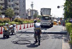 道路上に倒れた電柱の撤去に取り組む中部電力の作業員