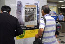 鉄道各社が運転を見合わせる中、駅構内に張り出された号外に見入る男性(18日、JR大阪駅)