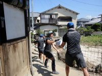 協力して土のうを運ぶ中国電力のラグビー部員
