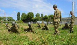 自衛隊員の指導の下、ほふく前進に取り組む新入社員