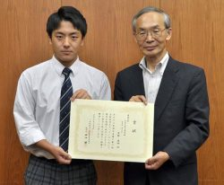 関東保安協・石田理事から最優秀賞の賞状を受け取る多摩工の花輪さん