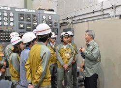 水力運転実習室で研修中の新入社員を激励する勝野社長(右)
