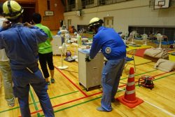 避難所となった野村中学校体育館でのスポットクーラー設置作業(11日、四国電力提供)