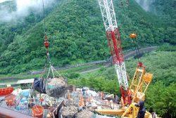 3工区、56号鉄塔の基礎工事現場で残土を運ぶ様子。谷間には国道と飛騨川、高山本線が走る