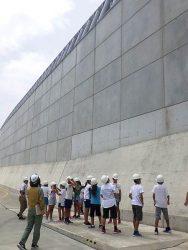発電所構内で高さ22メートルの防波壁を見学する児童ら