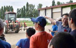 北大が研究を進めるロボットトラクターに関する説明を熱心に聞く参加者
