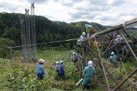 地滑りで倒壊した岩知志線の鉄塔から仮鉄柱へ移線する作業員(12日、北海道むかわ町)