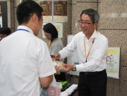 会場で売り子を務めた川崎社長(右)。抽選会でも自ら景品を渡した