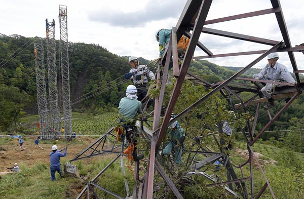 送電設備にも深刻な被害が発生した。岩知志線(6万6000V)では地滑りによって鉄塔が2基倒壊。写真は12日、倒壊した岩知志線の鉄塔から仮鉄柱へ移線する作業員(むかわ町)
