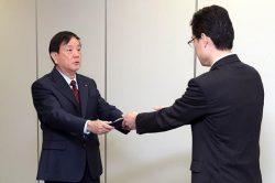 天野安全管理調査官(右)から認可書を受け取る和智副社長(7日、東京・六本木)