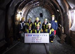 貫通した導水路トンネルで記念撮影する関係者