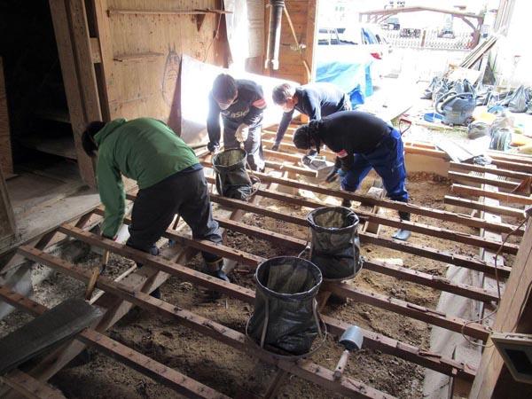 中国電力労働組合は、昨年7月の西日本豪雨で浸水被害を受けた岡山県倉敷市真備町地区でボランティア活動を継続的に実施している。写真は、浸水被害を受けた家屋床下の泥出し作業に取り組む組合員