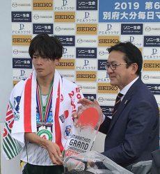 日本人トップでゴールした二岡選手(左)に 日本陸上競技連盟マラソン強化戦略プロジ ェクトリーダーの瀬古利彦氏からMGCチ ケットが手渡された